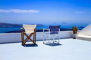 Two chairs looking out over Aegean Sea in Santorini Greece