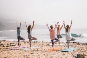 Women doing yoga on the beach