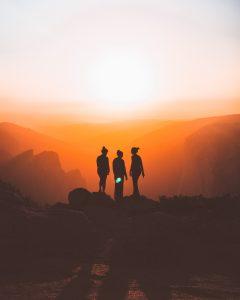 Three women hiking at sunset