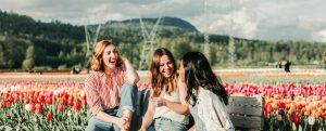Three women laughing in a flower field
