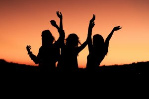 Three women dancing at sunset