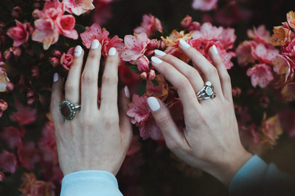 The best travel nail color is bright white, like the nail color on this woman's fingers, with her hands set against a bouquet of pink flowers.