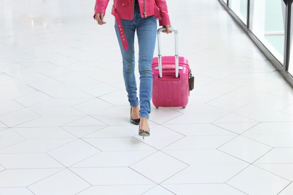 Solo female travel woman in pink jacket walking alone with pink carry on suitcase.