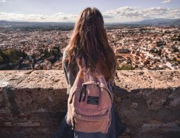 Solo female traveler with pink backpack overlooking crowded city