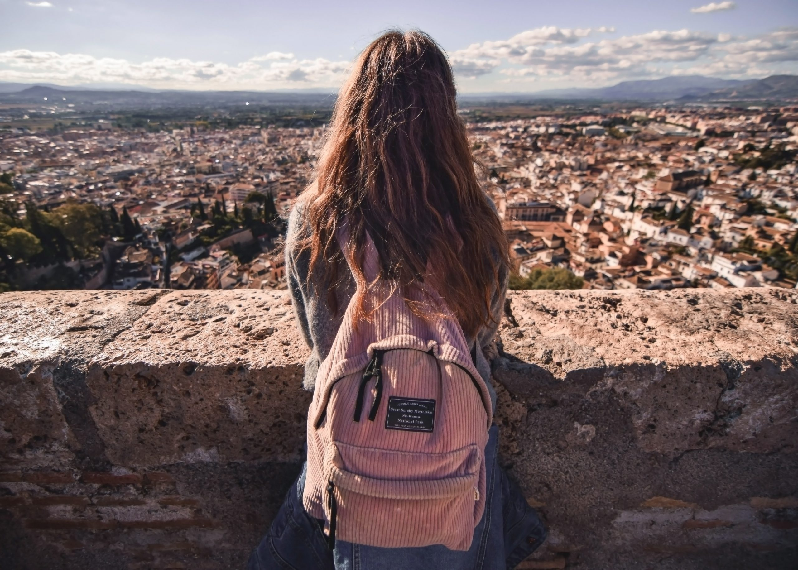 Solo female travel girl with pink backpack looking out at a crowded city.