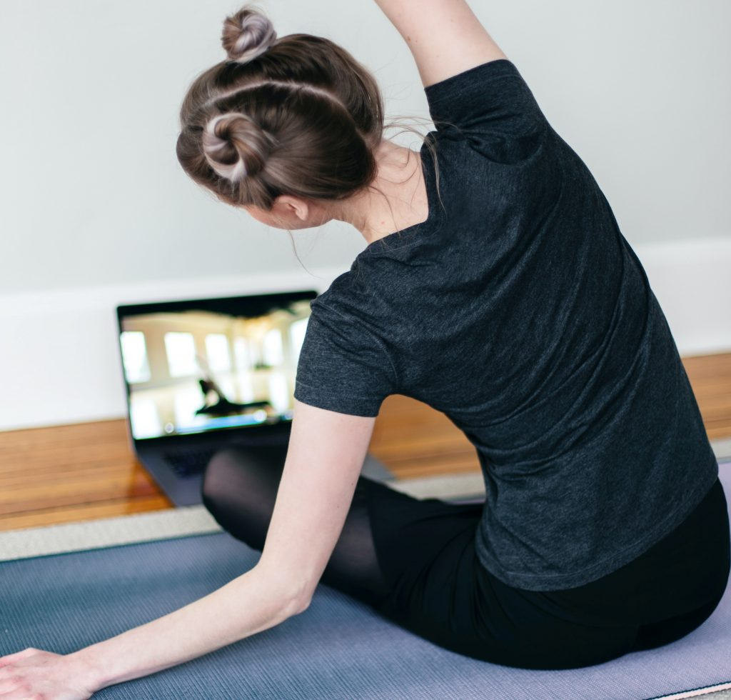 A woman does an at-home workout with the help of an app on her laptop.